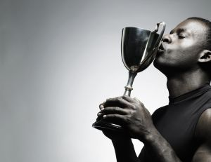 Young man kissing trophy, close-up