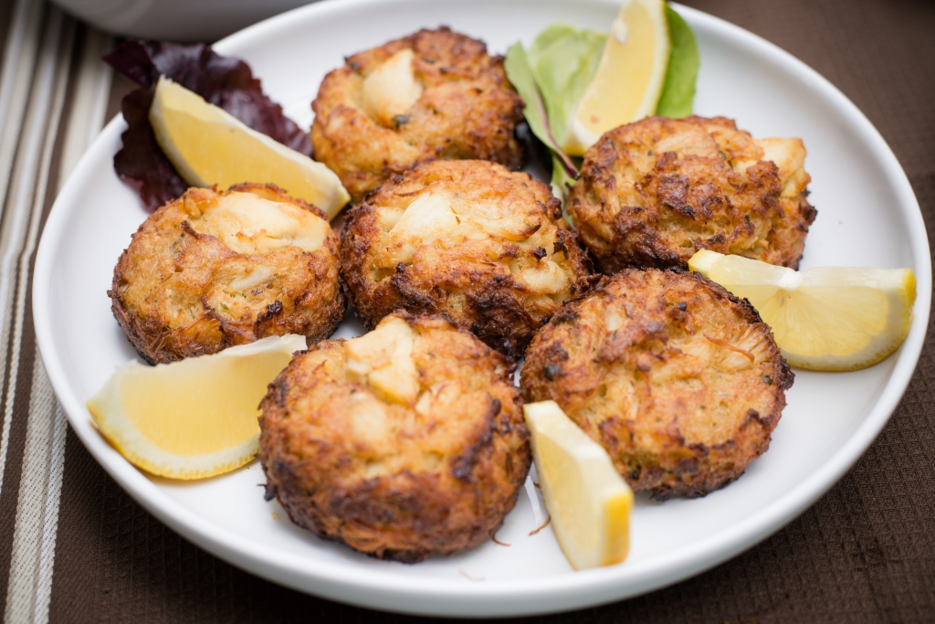 Crab cakes and lemon wedges on plate on table cloth