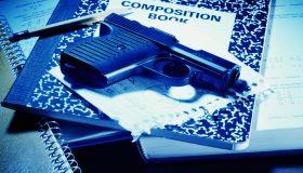 Handgun on school books, close-up
