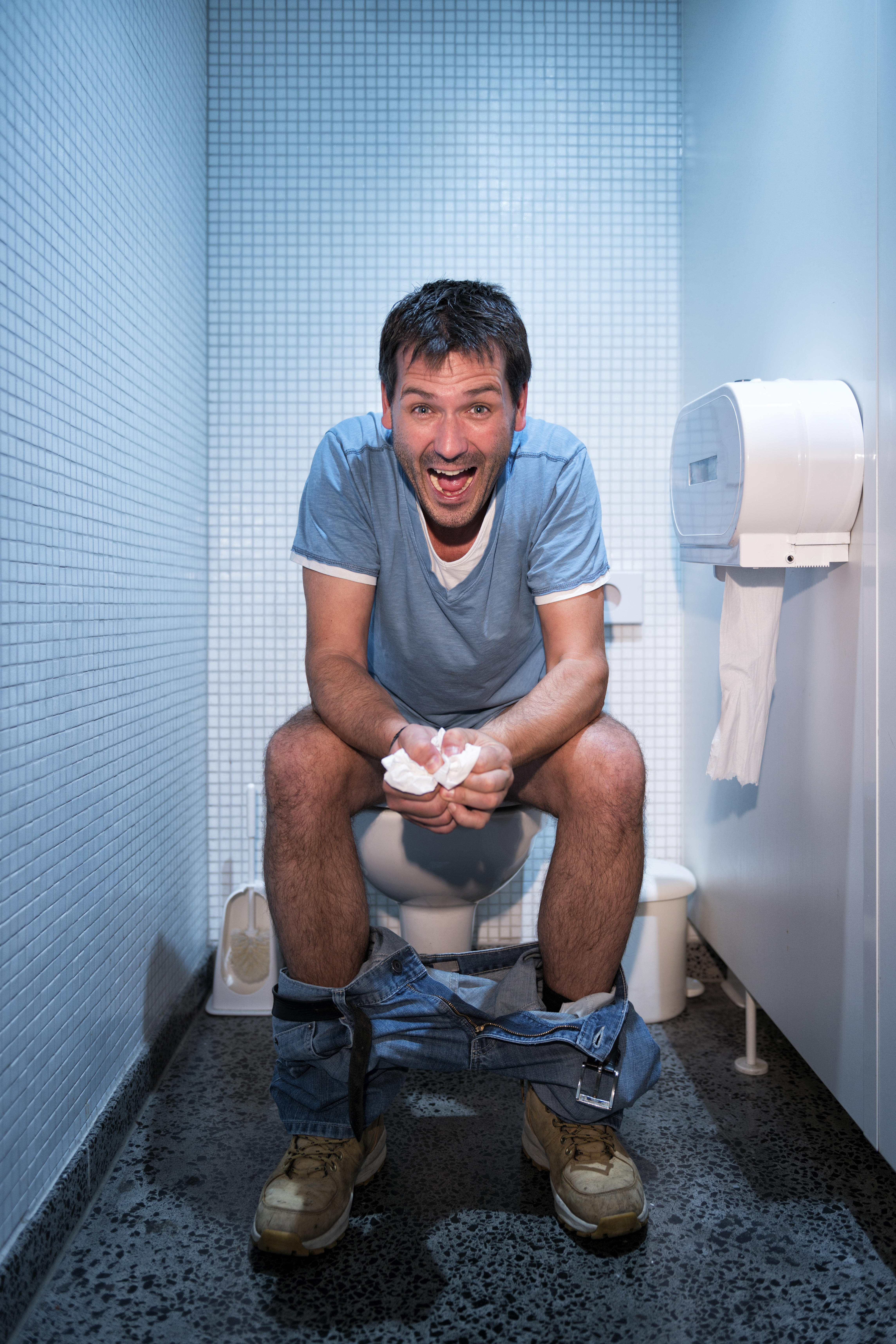 happy man sitting in public restroom
