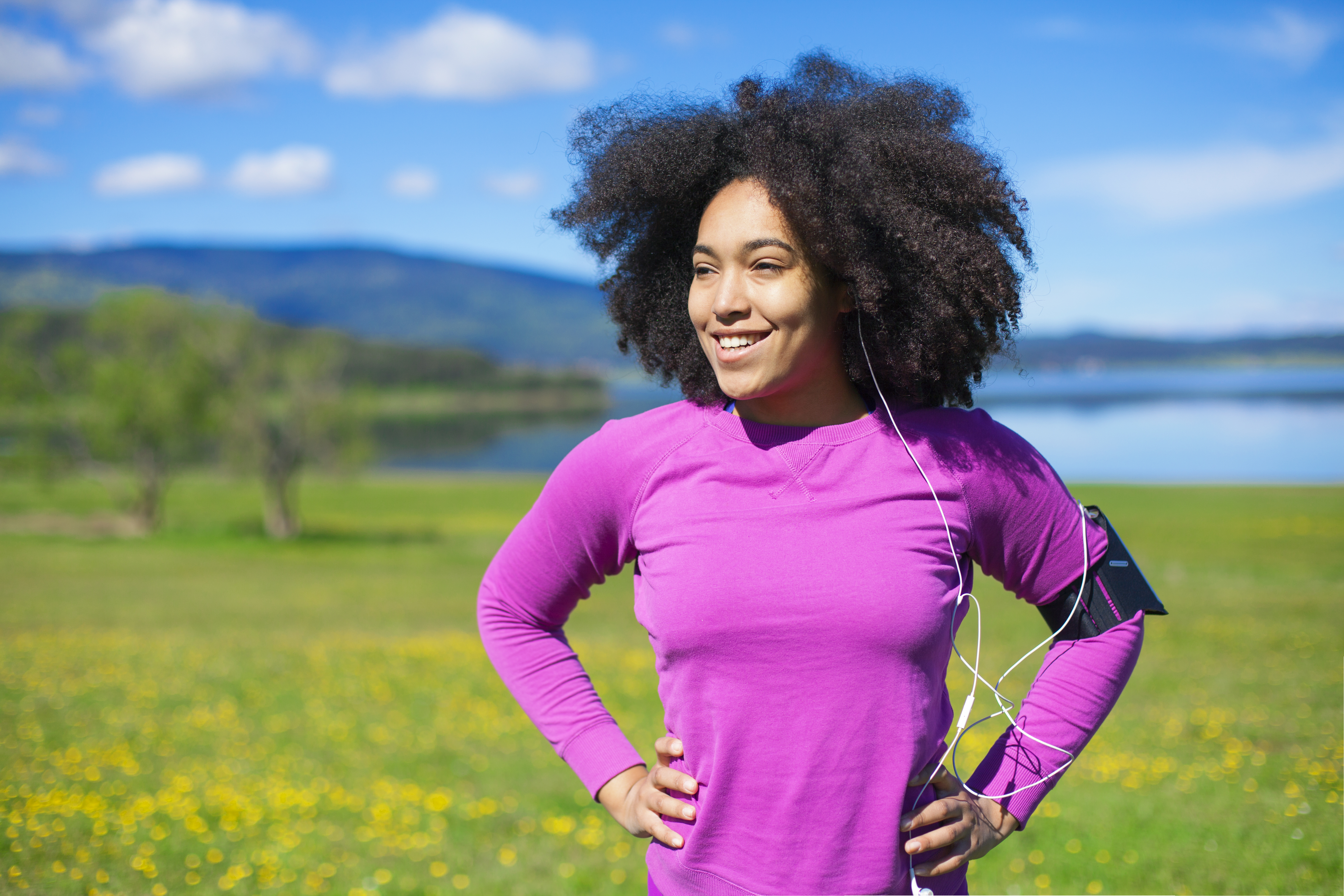 Woman relaxing from exercising in nature, wearing smart technology