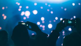 Audience members taking photos with mobile phones in a concert, against stage & spotlights