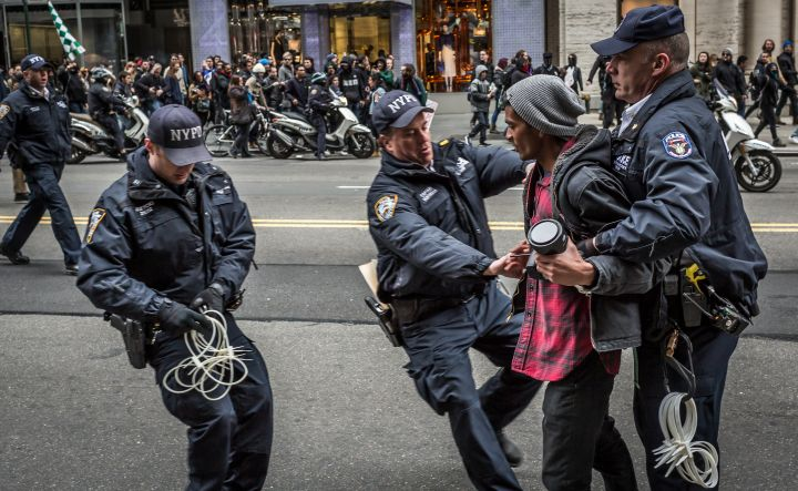 Policemen Arrest a Protester atan Anti-Trump Rally.