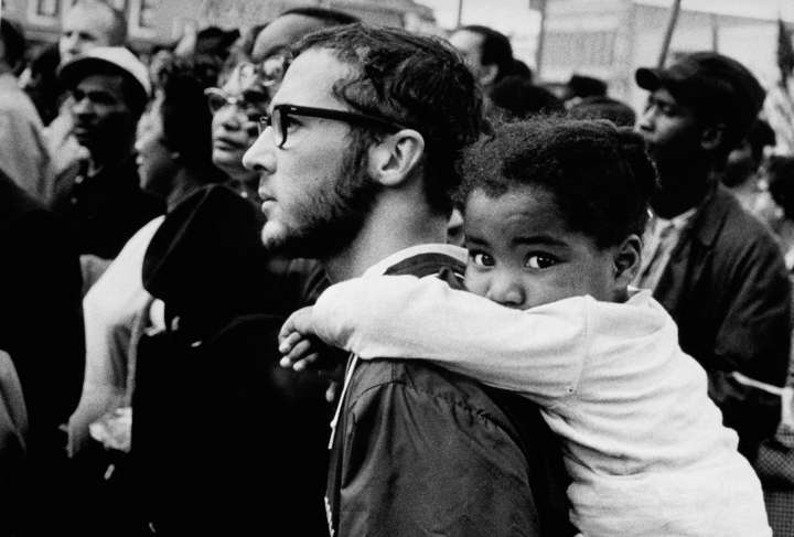 White Man Carrying Black Girl at March