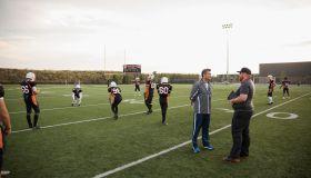 Coaches talking near teenage boy high school football team on football field