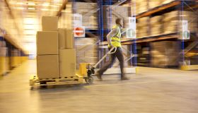 Blurred view of worker carting boxes in warehouse