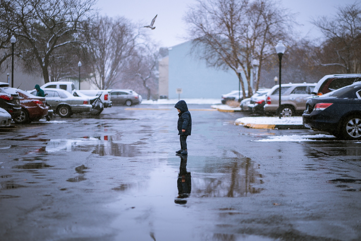 Side View Of Boy Standing On Wet Footpath During Winter