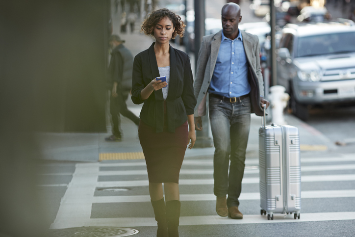 Businesswoman checking smartphone while walking on pedestrian crossing
