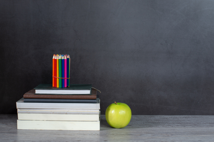 Stack of books and pencil on the table with blackboard background