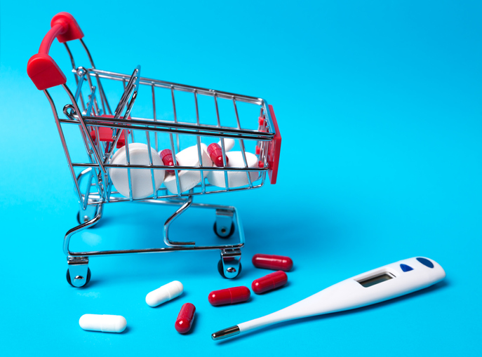 Pills and thermometer, tablets in the toy trolley for shopping on blue background. The concept of treating cold diseases.