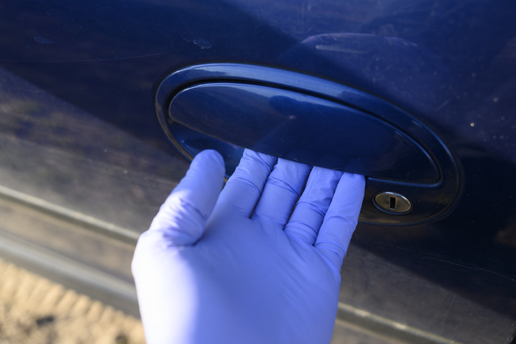 A unrecognisable person opening the door of a car with protective gloves outdoors.