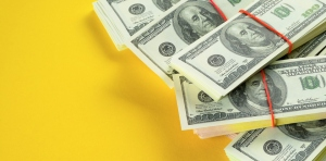 US dollars American Bills in Bundles On a Bright Yellow background.