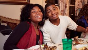 Smiling Black brother and sister at dinner table