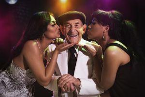 Hispanic women kissing senior man in nightclub